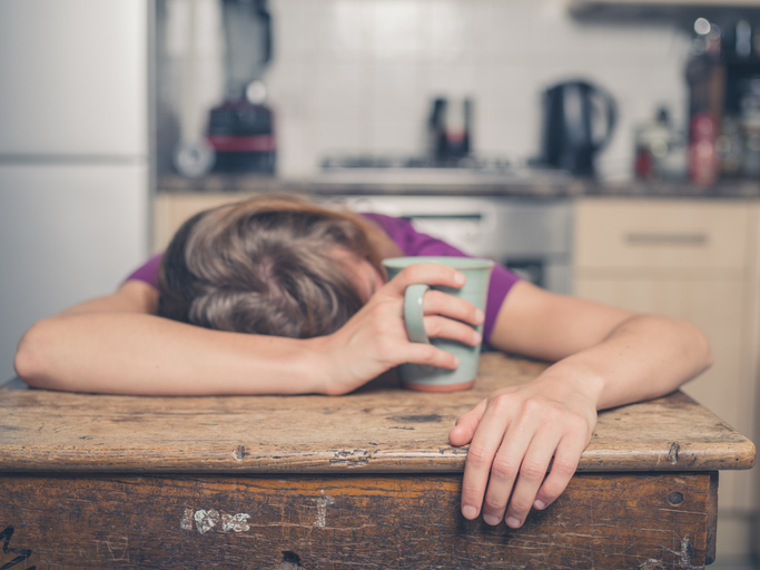 Tired woman with tea in kitchen